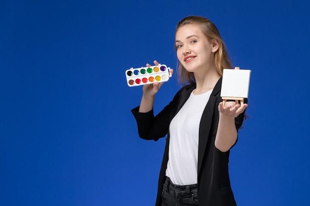 Studentin der vorderansicht in der schwarzen jacke, die rucksack hält farben für zeichnung und staffelei auf blauem schreibtisch zeichnet kunstschulhochschule Kostenlose Fotos