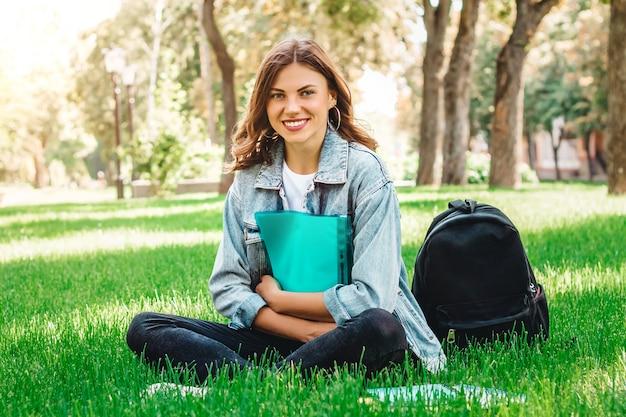 Studentin, die im park auf dem gras mit büchern und notizbüchern sitzt Premium Fotos