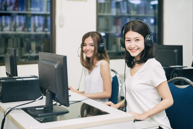 Studentin, die mit einem computer beim studieren in it-raum aufwirft. Premium Fotos