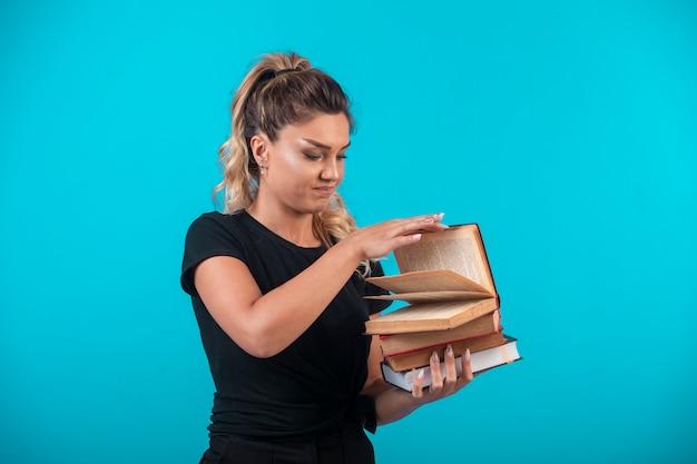 Studentin hält einen schweren vorrat an büchern und öffnet eines davon. Kostenlose Fotos