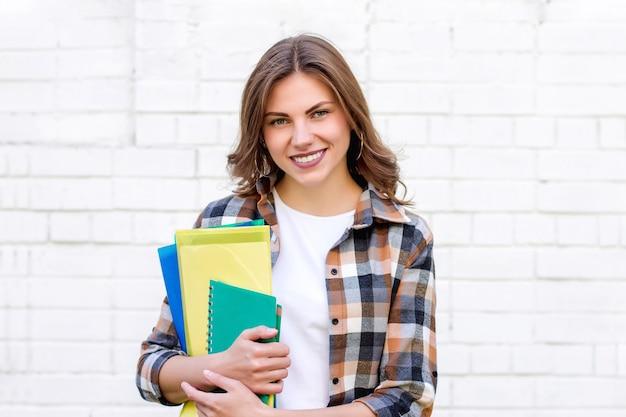 Studentin hält ordner und ein notizbuch in ihren händen und lächelt auf einem hintergrund einer weißen backsteinmauer Premium Fotos
