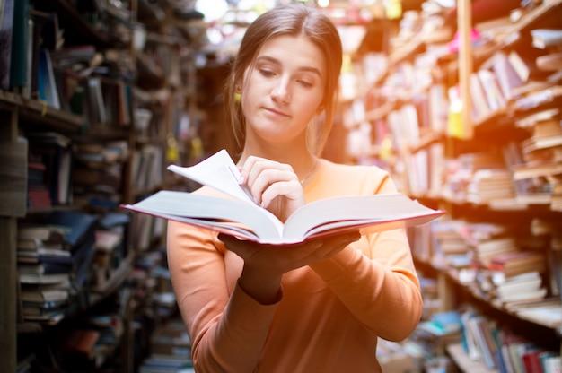 Studentin liest ein buch in der bibliothek, blättert um und bürstet informationen Premium Fotos
