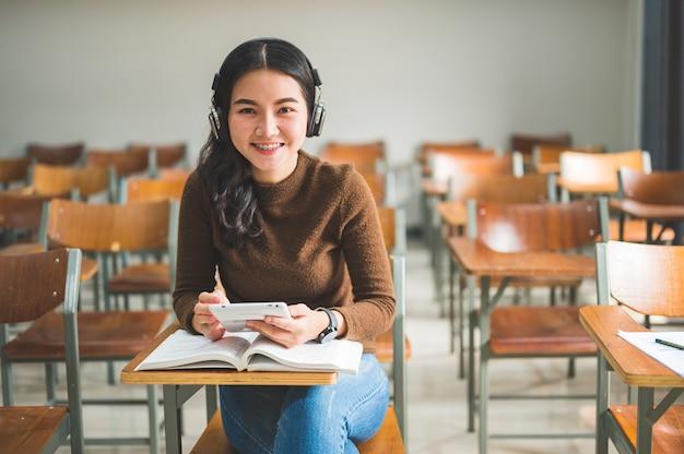Studentin sitzt und hört musik im klassenzimmer Premium Fotos