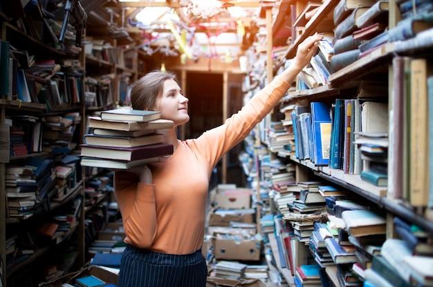 Studentin sucht in der alten bibliothek nach literatur, sie nimmt ein buch aus dem bücherregal, eine frau sucht nach informationen in den archiven Premium Fotos