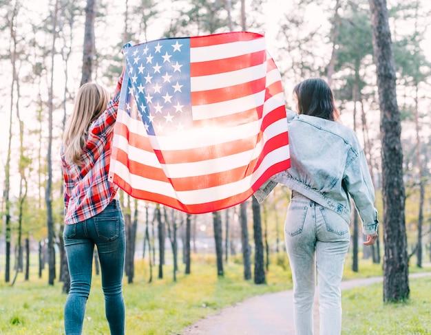 Studentinnen, die draußen flagge von usa halten Kostenlose Fotos