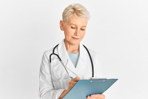 Studioaufnahme der attraktiven blonden ärztin mittleren alters mit stethoskop um ihren hals, die isoliert mit stift und zwischenablage aufwirft, medizinische aufzeichnungen macht, behandlung für patienten verschreibend Kostenlose Fotos