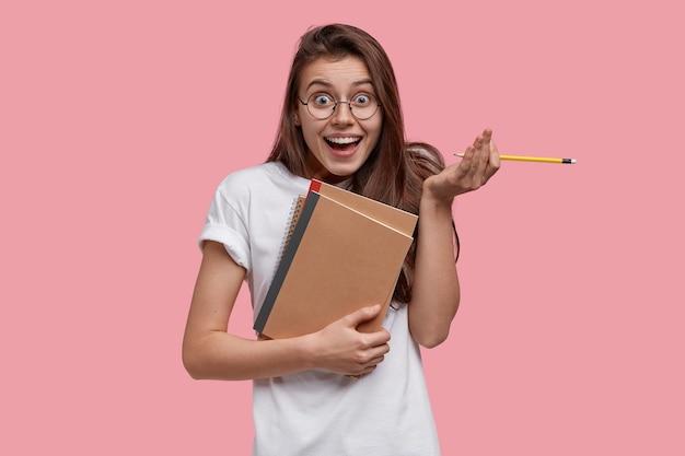 Studioaufnahme der erfreuten dunkelhaarigen frau hält bleistift, lehrbücher, sieht glücklich aus, fühlt sich froh, die arbeit zu beenden, bereitet hausaufgabe vor Kostenlose Fotos