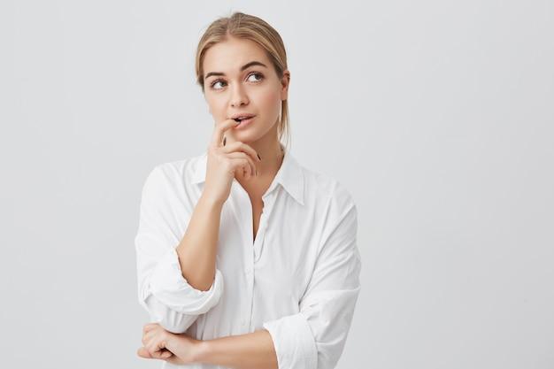 Studioaufnahme der gerissenen schönen frau mit dem geraden blonden haar, das beiseite hält hand unter kinn hält, um kniffligen plan zu verwirklichen. Kostenlose Fotos