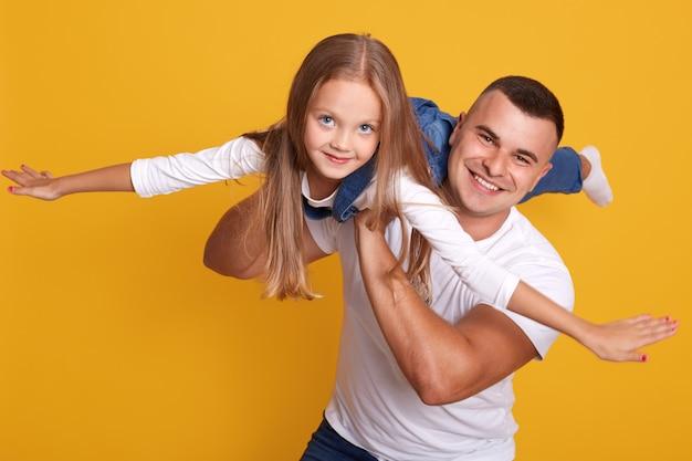 Studioaufnahme des glücklichen familienvaters und der tochter, die zusammen spielen, niedliches kind, das overalls trägt und vorgibt, mit ihren händen flugzeug zu sein Kostenlose Fotos