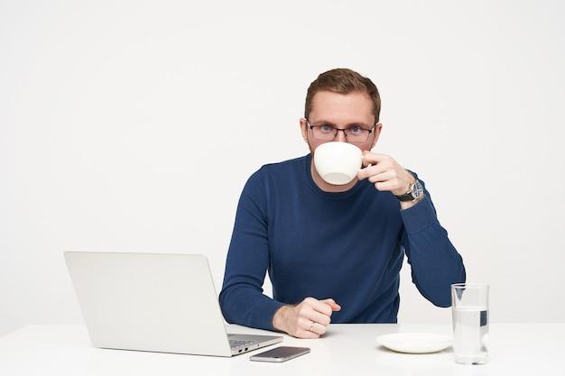 Studioaufnahme des jungen bärtigen mannes in den gläsern, die kaffeepause beim arbeiten mit seinem laptop und beim betrachten der kamera, gekleidet im blauen pullover beim sitzen über weißem hintergrund Kostenlose Fotos
