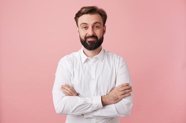 Studioaufnahme des positiven jungen brünetten mannes mit bart, der trendige frisur trägt, während vorne mit leichtem lächeln betrachtet, formelle kleidung tragend, während über rosa wand posierend Kostenlose Fotos