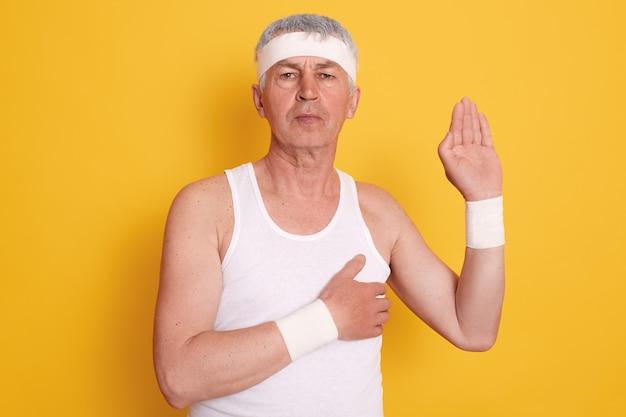 Studioaufnahme eines ernsthaften konzentrierten reifen mannes, der gegen gelbe wand aufwirft und weißes ärmelloses t-shirt und stirnband trägt Kostenlose Fotos