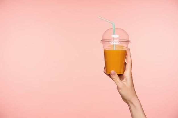 Studiofoto der erhabenen gepflegten frauenhand mit der nackten maniküre, die plastikbecher des orangensaftes mit stroh hält, während über rosa hintergrund lokalisiert wird Kostenlose Fotos