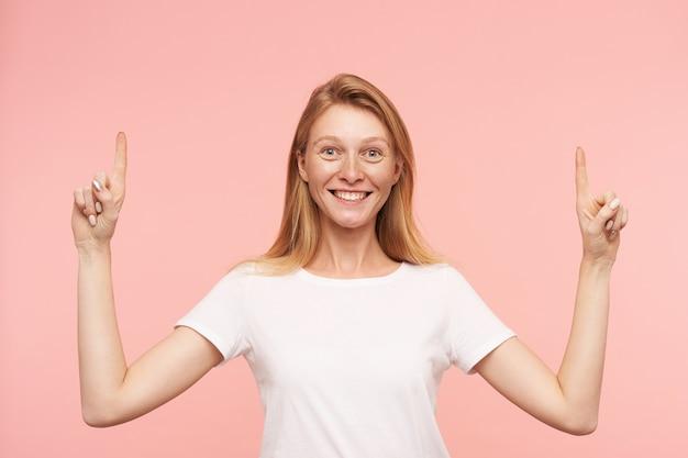 Studiofoto der jungen attraktiven frau mit dem losen foxy haar, das fröhlich in die kamera lächelt und zeigefinger angehoben hält, über rosa hintergrund stehend Kostenlose Fotos