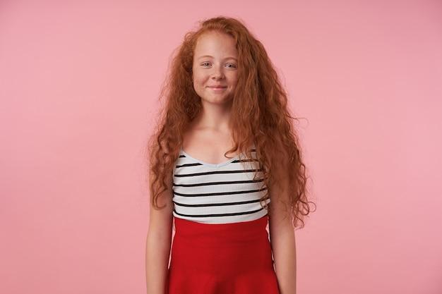 Studiofoto des hübschen rothaarigen mädchens mit dem langen lockigen haar, das über rosa hintergrund mit händen unten aufwirft, kamera mit charmantem lächeln betrachtend, roten rock und gestreiftes oberteil tragend Kostenlose Fotos