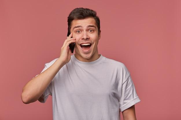 Studiofoto des jungen hübschen dunkelhaarigen mannes mit dem kurzen haarschnitt, der über rosa hintergrund aufwirft, zur kamera glücklich mit geöffnetem weitem mund schauend, handy in der hand haltend Kostenlose Fotos