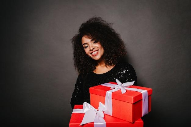 Studioporträt der glückseligen lockigen frau, die geschenke hält Kostenlose Fotos