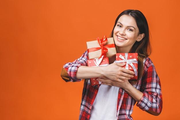 Studioporträt der lächelnden jungen schönen frau hält rote geschenkboxen. isoliert gegen orange hintergrund. Premium Fotos