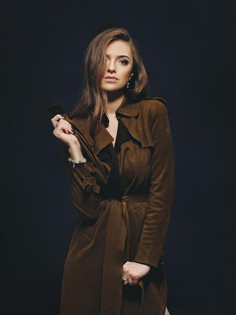Studioporträt eines jungen modemodells, das einen mantel mit einer dunklen wand im hintergrund trägt Premium Fotos
