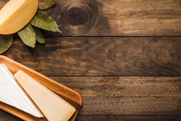 Stück käse auf hölzernem behälter mit lorbeer verlässt gegen ...