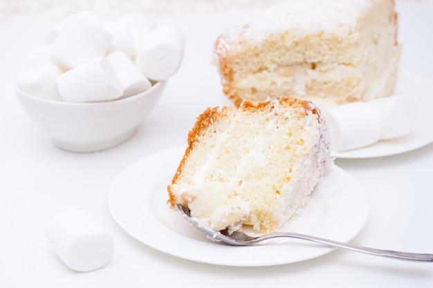 Stück kuchen mit weißen sahne- und kokosnusschips und eibischen Premium Fotos