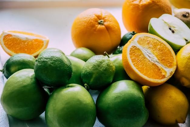 Stück orange, apfel und zitrone auf dem weißen hintergrund Premium Fotos