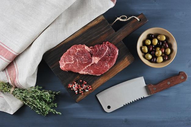 Stück rindfleisch auf einem holzbrett, ein messer für fleisch, oliven und thymian Premium Fotos