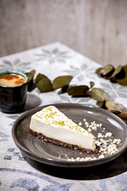 Stück roher veganer käsekuchen, kein backen glutenfrei, dekoriert mit limettenschale und cashewnüssen auf teller Premium Fotos
