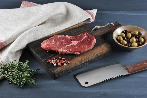 Stück rohes rindfleisch auf einem holzbrett, ein messer für fleisch, oliven und thymian Premium Fotos