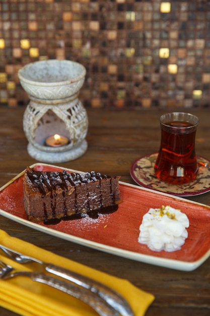 Stück schokoladen-brownie serviert mit sahne und tee Kostenlose Fotos