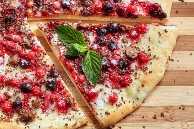 Stück süße pizza mit johannisbeere, roter johannisbeere, minze und schokolade Premium Fotos