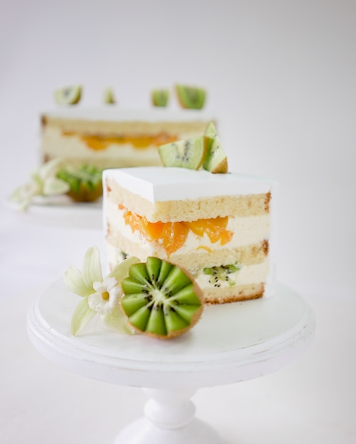 Stück vanillekuchen mit frischer kiwi und pfirsichen auf weißem hölzernem kuchenstand Premium Fotos