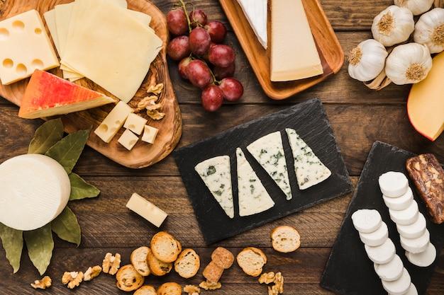 Stück verschiedene käsesorten mit trauben; brotscheibe; walnuss und knoblauch auf dem schreibtisch Kostenlose Fotos