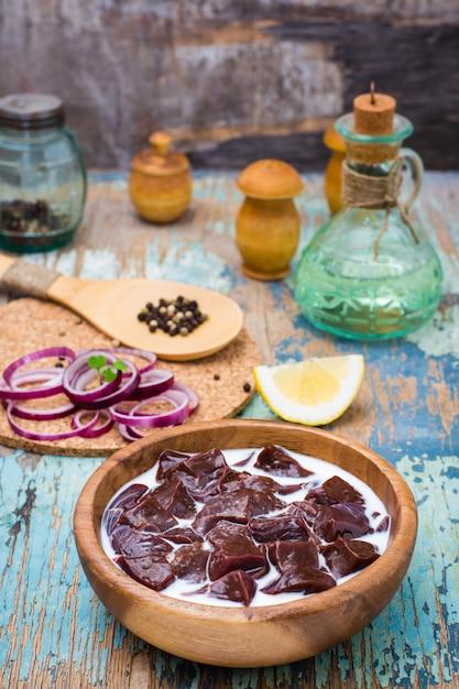Stücke der rohen rindfleischleber getränkt in der milch in einer hölzernen schüssel und in den bestandteilen für auf dem tisch kochen Premium Fotos