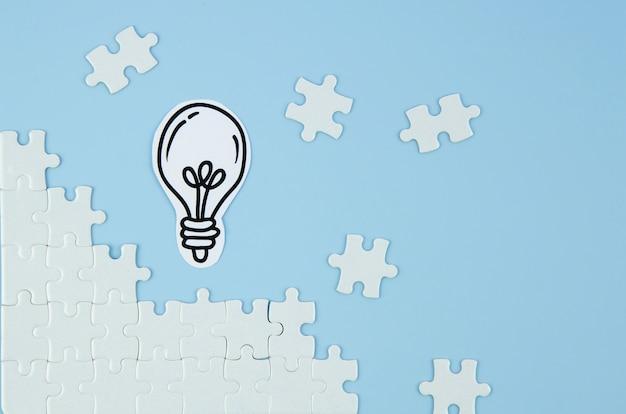 Stücke des puzzlespiels mit glühlampe auf blauem hintergrund Premium Fotos