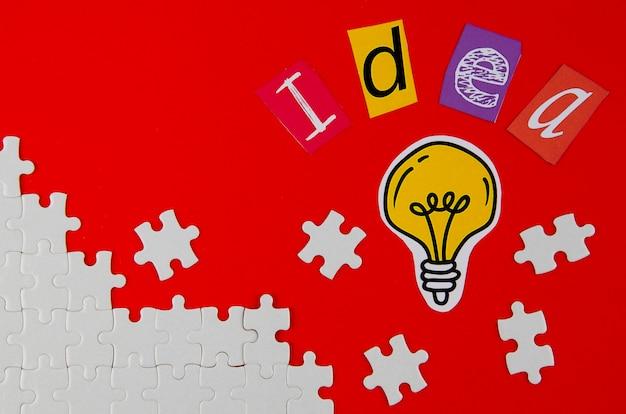 Stücke des puzzlespiels mit glühlampe auf rotem hintergrund Kostenlose Fotos