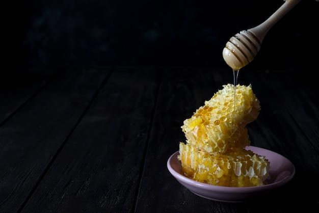 Stücke frische bienenwabe mit einem hölzernen schöpflöffel, der honig auf einer keramischen platte tropft Premium Fotos