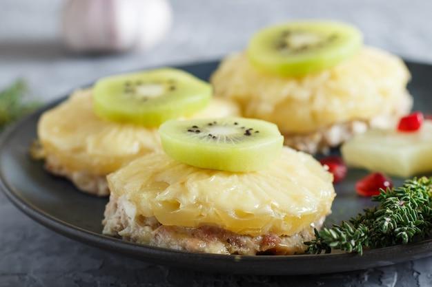 Stücke gebackenes schweinefleisch mit ananas, käse und kiwi auf grau Premium Fotos