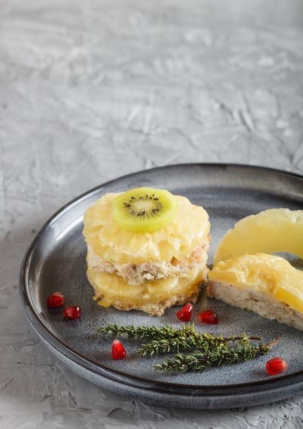 Stücke gebackenes schweinefleisch mit ananas, käse und kiwi auf grauer platte. Premium Fotos