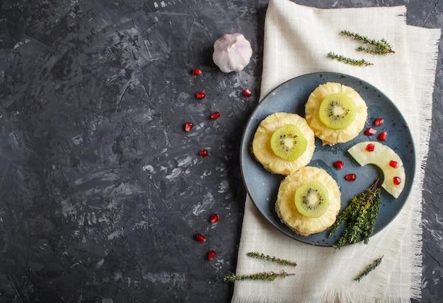 Stücke gebackenes schweinefleisch mit ananas, käse und kiwi auf schwarzem hintergrund. Premium Fotos