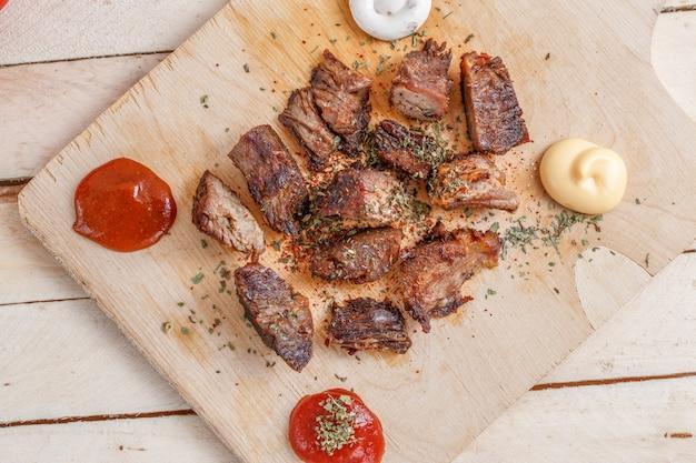 Stücke gebratenes fleisch mit gewürzen auf einem hölzernen behälter mit vier arten soßen zum fleisch Premium Fotos