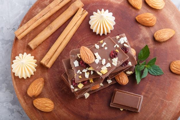 Stücke milchschokolade mit mandeln und trockenfrüchten Premium Fotos
