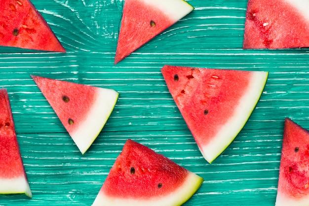 Stücke rote wassermelone auf grünem hintergrund Kostenlose Fotos