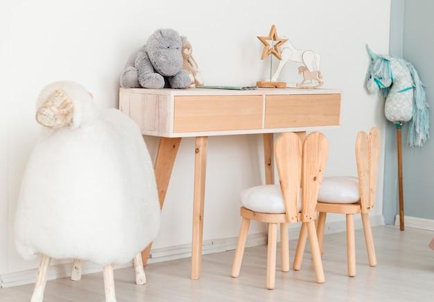 Stühle mit hasenohren im kinderzimmer, ein tisch mit spielzeug und ein großes schaf Premium Fotos