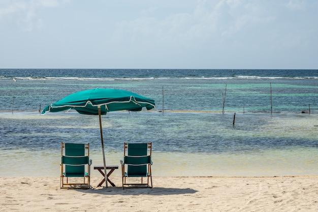 Stühle und ein großer sonnenschirm am strand an einem klaren, sonnigen tag Kostenlose Fotos
