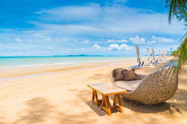 Stuhl und tabelle, die auf dem strand und dem meer mit blauem himmel speisen Kostenlose Fotos