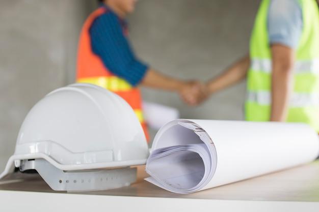 Sturzhelm und blaupause auf tabelle mit ingenieurteam rütteln handhintergrund Premium Fotos
