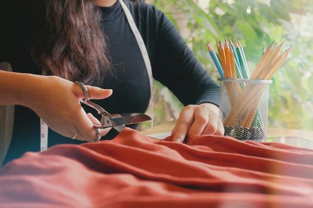 Stylish fashion designer schneiden stoff der neuen kollektion im atelier. kreatives designkonzept. Premium Fotos