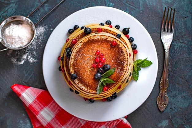 Süß gebackene hausgemachte pfannkuchen mit beeren, minze und puderzucker zum frühstück. draufsicht Premium Fotos
