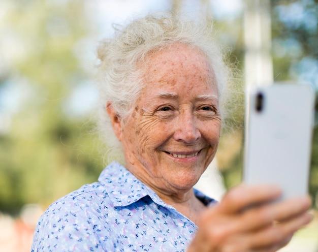 Süße ältere frau, die ein selfie nimmt Premium Fotos
